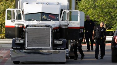 San Antonio police officers investigate the semi trailer where the gruesome discovery was made.