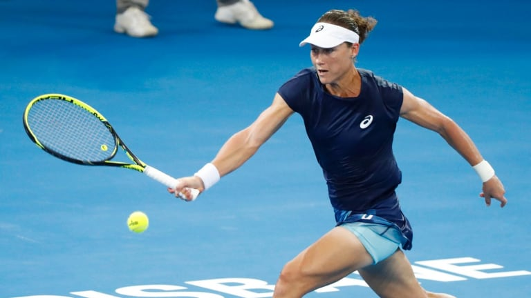 Stretch: Stosur reaches for a shot in a rally with Anastasija Sevastova of Latvia in their first-round match at the Brisbane International.
