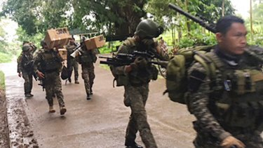 Philippine troops arrive at their barracks to reinforce fellow troops following the siege by Muslim militants in the outskirts of Marawi city in southern Philippines.