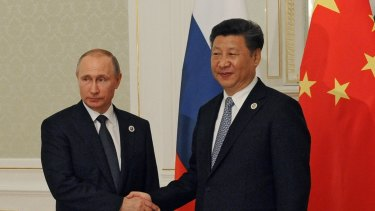 Russian President Vladimir Putin, left, and Chinese President Xi Jinping shake hands during their meeting at a summit in Tashkent, Uzbekistan.