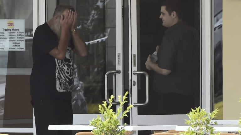 Fatal shooting: A man with his head in his hands at Hungry Jack's, Hoxton Park.