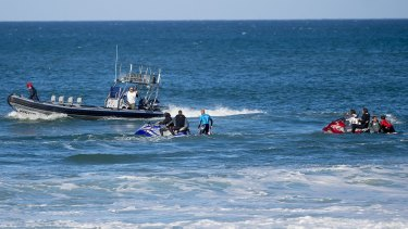 Mick Fanning (in blue) and Julian Wilson (red) are taken to the safety boat after Fanning was attacked by a shark during the final of the J-Bay Open on Sunday.