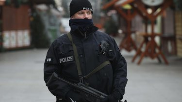 A heavily-armed policeman stands at the site of the attack.