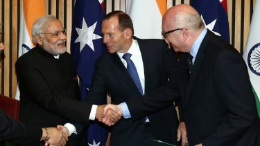 Indian Prime Minister Narendra Modi shakes hand with then prime minister Tony Abbott and Attorney-General George Brandis during his 2014 visit to Australia.