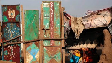 Children peek from their family's hut at a camp for internally displaced people near Abs, Yemen.
