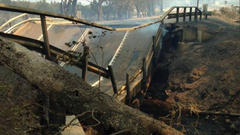 The intense heat of the bushfire has caused the Samson Brook bridge asphalt to buckle and collapse. Photo: Nine News Perth via WA Today 7th January 2016