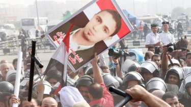 Egyptian anti-Mubarak protesters, carrying a photo of a killed protester, clash with riot police in Cairo in 2011.