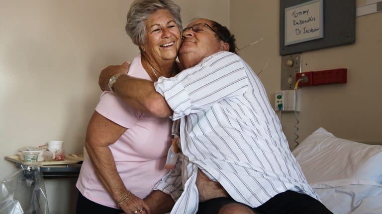 Tommy Raudonikis with his partner Trish Brown in his hospital room.