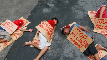 """People stage a """"die-in"""" to protest the rising number of extra judicial killings related to Philippine President Rodrigo Duterte's """"War on Drugs""""."""