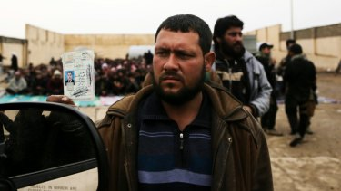 Fleeing: A man holds up his identification card to an Iraqi intelligence officer screening men and boys escaping Mosul.