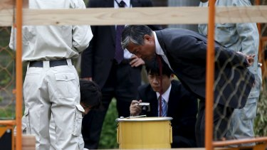 Workers of Tokyo's Toshima ward office and police officers check a container holding a fragment of an unknown object after it was dug up from the ground near playground equipment at a park in Toshima ward, Tokyo.