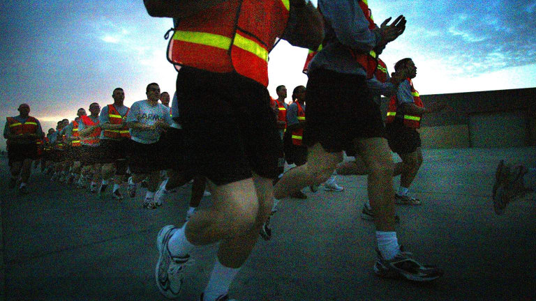 A US platoon sergeant leads his men and women in a run along one of the perimeter fences for their daily physical training in the early hours of the morning in Qatar in a file picture.
