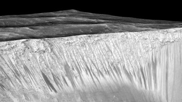 The dark streaks are about 100-metres long and flow down the side of a crater.