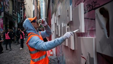 "A ""council worker"" paints over art pieces by street artist Lush in Hosier Lane."