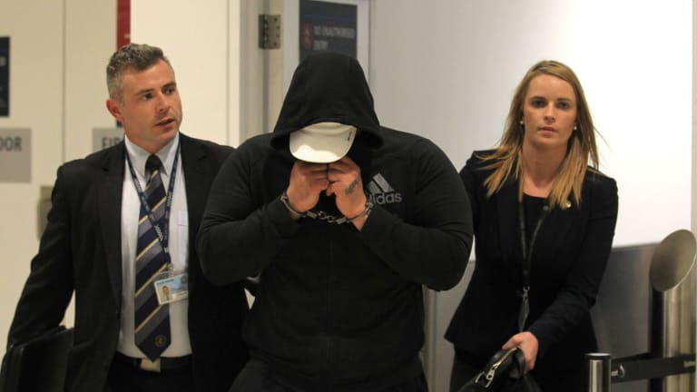 'Brownie' Ahmad, pictured with two detectives, was arrested after he stepped off a flight from Doha.