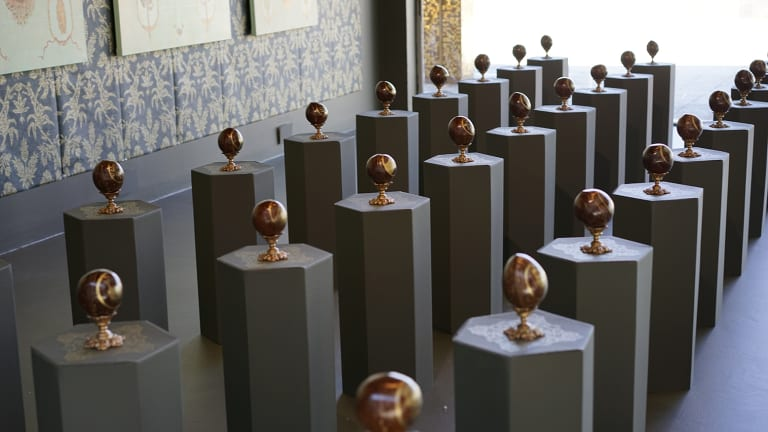 """Painted coconuts referencing the importance of the exchange of goods and the process of material exchange between voyagers and Indigenous peoples in the Nicola Dickson exhibition """"Close Encounters"""" at Canberra Museum and Gallery."""