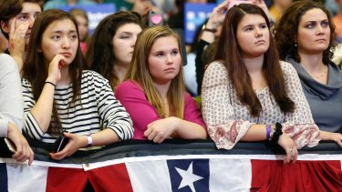 Young women listen to first lady Michelle Obama speak during a campaign rally for Democratic presidential candidate Hillary Clinton.