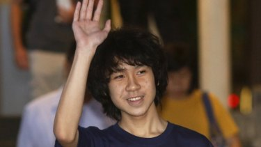Amos Yee waves as he leaves court in Singapore.