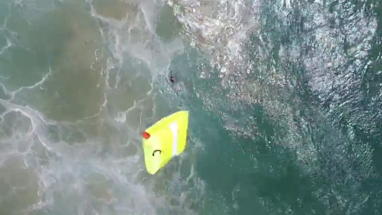 The drone dropped the flotation device to the swimmers.