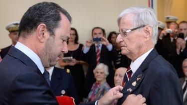 Denis Kelly receives the Legion d'Honneur from ambassador Christophe Lecourtier.