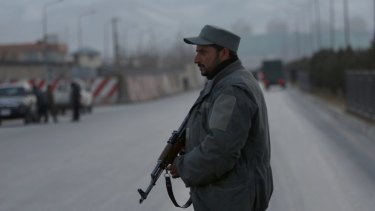 A member of the Afghan security forces stands guard near the site of two blasts in Kabul last month.