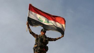 A member Iraq's elite counterterrorism forces raises an Iraqi flag after retaking Bartella, outside Mosul.