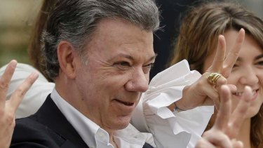 Colombia's President Juan Manuel Santos makes the victory sign after voting in a referendum in October.