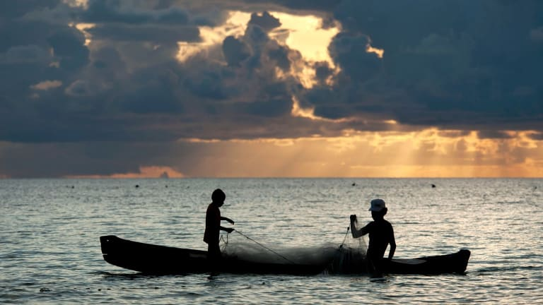 Father and son fishermen in dugout canoe bringing in a net at sunset, Ohoidertutu Village, Kei Islands, Moluccas, Indonesia.