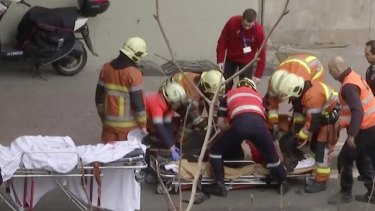 Emergency rescue workers stretcher a person at the site of an explosion at a metro station in Brussels.