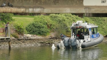 A child looks on as police retrieve another suspicious object from the river in February.