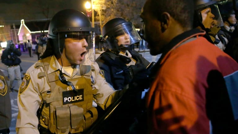 Police confront protesters after the announcement of the grand jury decision not to indict police officer Darren Wilson in the fatal shooting of Michael Brown in November last year.