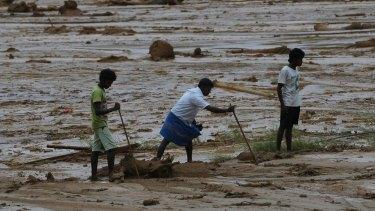 Sri Lankan landslide survivors try to salvage their belongings buried in the mud after a landslide in Elangipitiya village on Wednesday.