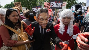 A demonstrator dressed as Tony Blair, with painted red hands and in handcuffs, protests Britain's involvement in the Iraq war in London on Wednesday.
