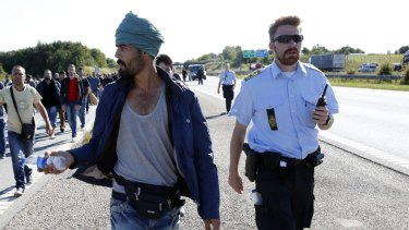 Not in my backyard: Migrants walk north on a highway in southern Denmark. Danish police in September closed a motorway and rail links with Germany as migrants headed north to Sweden.
