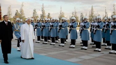 Pomp and ceremony:  Pope Francis and Turkish President Recep Tayyip Erdogan, left, walk by the honour guard at the presidential palace in Ankara.