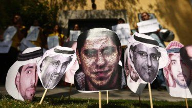 A photo of Saudi blogger Raif Badawi (centre) with photos of other prisoners in Saudi Arabia at a protest in Mexico calling for his release.