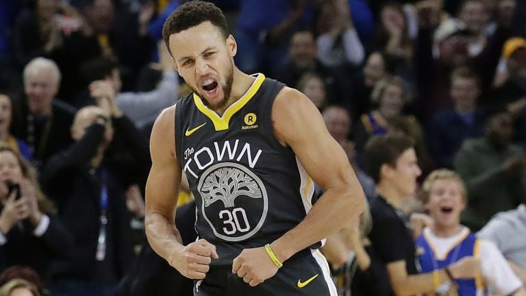 Golden State Warriors guard Stephen Curry reacts after scoring during the first half of the team's NBA basketball game against the Memphis Grizzlies.