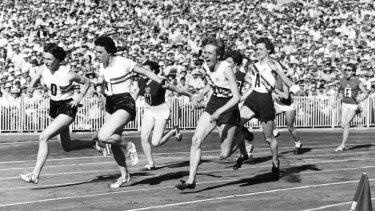 Betty Cuthbert takes the baton from Fleur Mellor on the final leg in the 4x100 metres relay at the Melbourne Olympics.