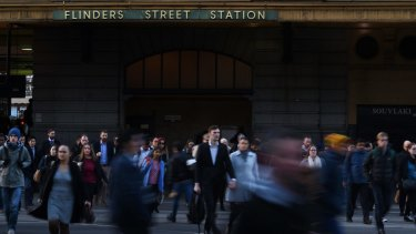 Commuters pour out of Flinders Street Station.