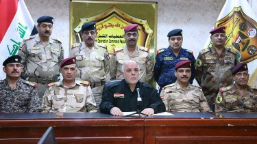 Iraqi Prime Minister Haider al-Abadi (centre, in black) has declared the city of Mosul liberated from Islamic State.