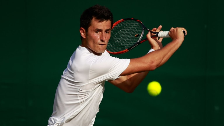 Bernard Tomic in action against Roberto Bautista Agut of Spain.