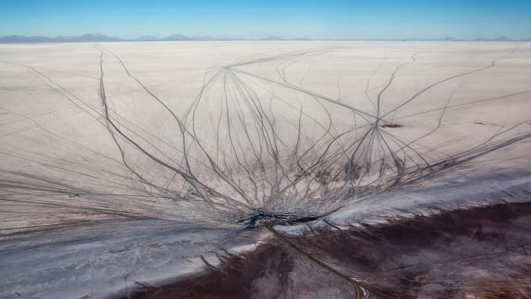 Vehicle tracks scar the Salar de Uyuni.