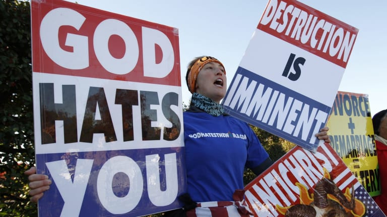 Members of the American Westboro Baptist Church hold anti-gay signs at a protest.