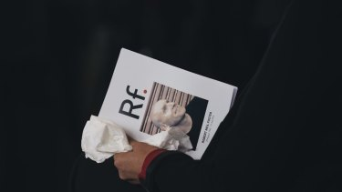 A mourner with the program for the funeral.