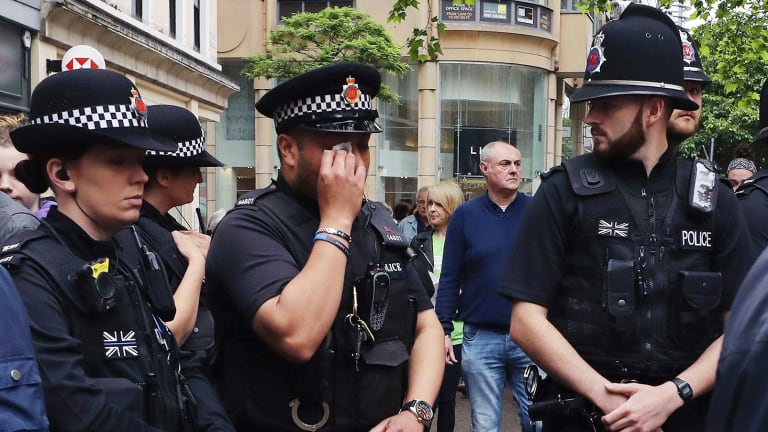 A police officer wipes away tears as he looks at flowers and tributes left in St Ann's Square in Manchester, England.