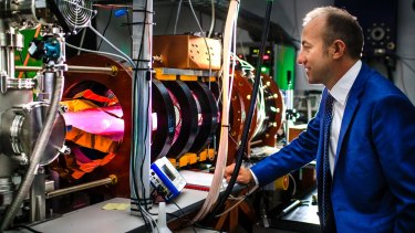 Director of the Australian Plasma Fusion Research Facility at ANU Dr Cormac Corr with the glowing MAGPIE II - a machine used to test plasma interactions.
