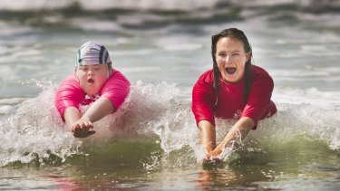 Georgia Brown, 12, is part of the Starfish Nippers program at the Anglesea Surf Club. She is photographed with her trainer Greta Dickson learning how to swim in the surf.