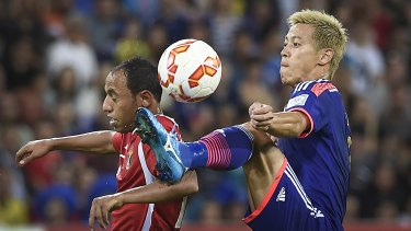 Jordan's Monther Abu Amara and Japan's Keisuke Honda compete for the ball during the Asian Cup match on Tuesday.