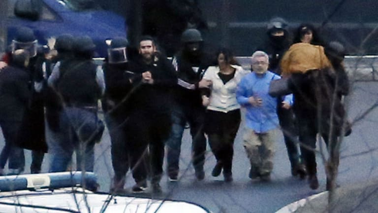 Members of the French police special forces evacuate the hostages after launching the assault at a kosher grocery store.