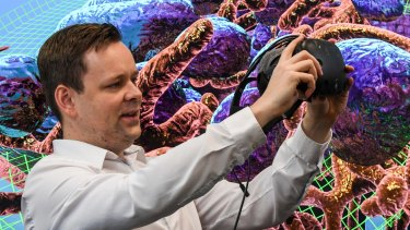 UNSW's John McGhee holds the virtual reality mask that allows you to explore inside a breast cancer cell. Mitochondria and endosomes form the backdrop.
